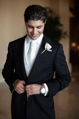 Groom wearing silver vest and white tie