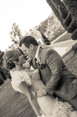 Black and white photo of bride in ruffle Mark Zunino wedding dress bolero with groom in suit