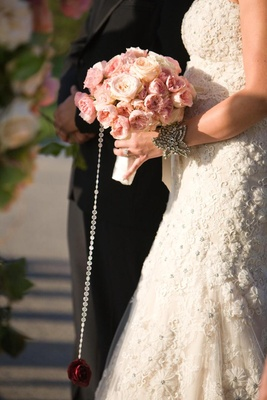Bride walking down aisle with red rose hanging from bouquet