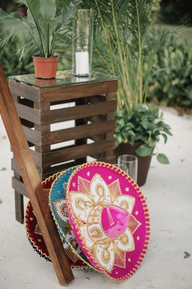 Wedding reception photo booth set up wood details swing on sand with pink magenta and blue sombrero