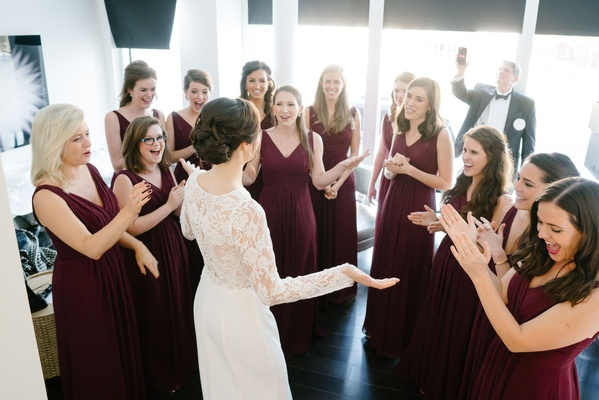 Bride in white wedding dress long sleeve showing bridesmaids her dress bridesmaid burgundy gowns