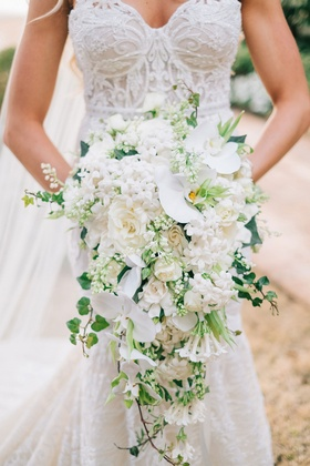 Bride in Berta wedding dress holding cascade bouquet cascading with white orchid flowers greenery