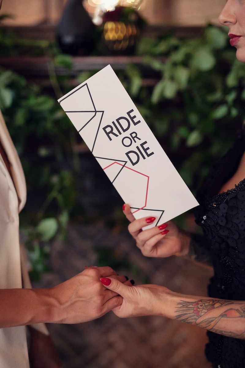 "Wedding ceremony with bride reading vows from a card with ""Ride or Die"" on the cover"