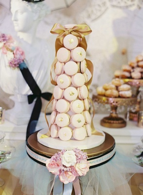 Tower of light pink French macarons with gold flakes at wedding dessert bar