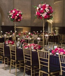 black linens, gold chiavari chairs, bright pink flowers