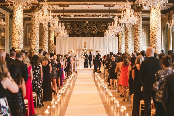 wedding ceremony candles along aisle guests standing wood cross at altar