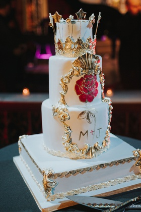 three layer wedding cake on white gold stand with hand painted flowers gold details crown