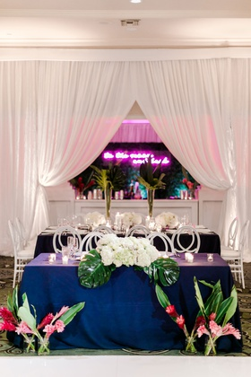 wedding reception sweetheart table navy blue linens pink tropical flowers greenery palms neon sign