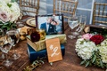 wedding table number held with books, framed engagement photo on top