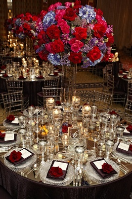 Mirrored tabletop with Lucite chairs and bright centerpiece