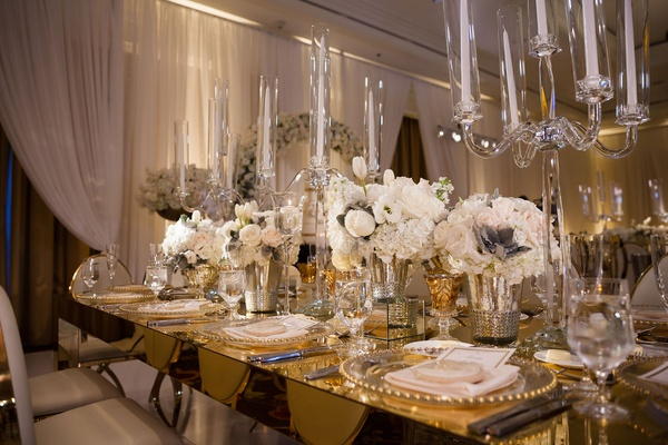 Gold mirror table with white chairs low ivory flower arrangements and tall crystal candelabra taper