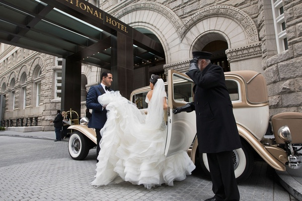 Driver opening door for bride in voluminous gown groom holding skirt classic car