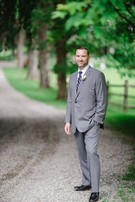 groom in custom grey brooks brothers suit, blue and pink striped tie