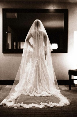 Black and white photo of bride looking in mirror