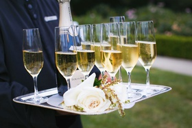 champagne in flutes with white roses on silver tray held by server