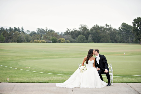 bride in reem acra, groom in white tie tuxedo, bride and groom on bench at golf course