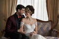 bride in lace dress and gold headpiece smiling at groom dark burgundy and black suit orange bow tie