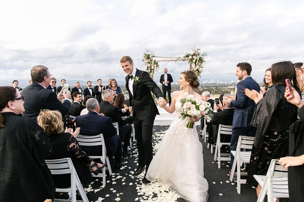 wedding guests standing and clapping high five couple after rooftop wedding ceremony view of city