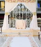 chuppah with white drapery, blush and ivory roses, and hanging orchids