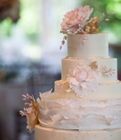 delicate five tier white wedding cake with pink flowers and gold detailing ruffles