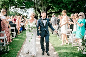 bride in wedding dress groom in blue tuxedo guests on grass lawn south carolina destination wedding