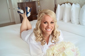 bride in robe, blue badgley mischka heels lying on bed