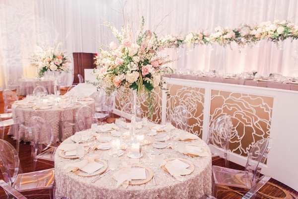 Tall wedding centerpiece on texture linen round table with white pink green flowers ballroom