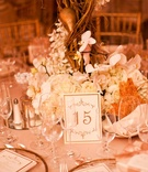 Gilt table assignment in front of white floral centerpiece