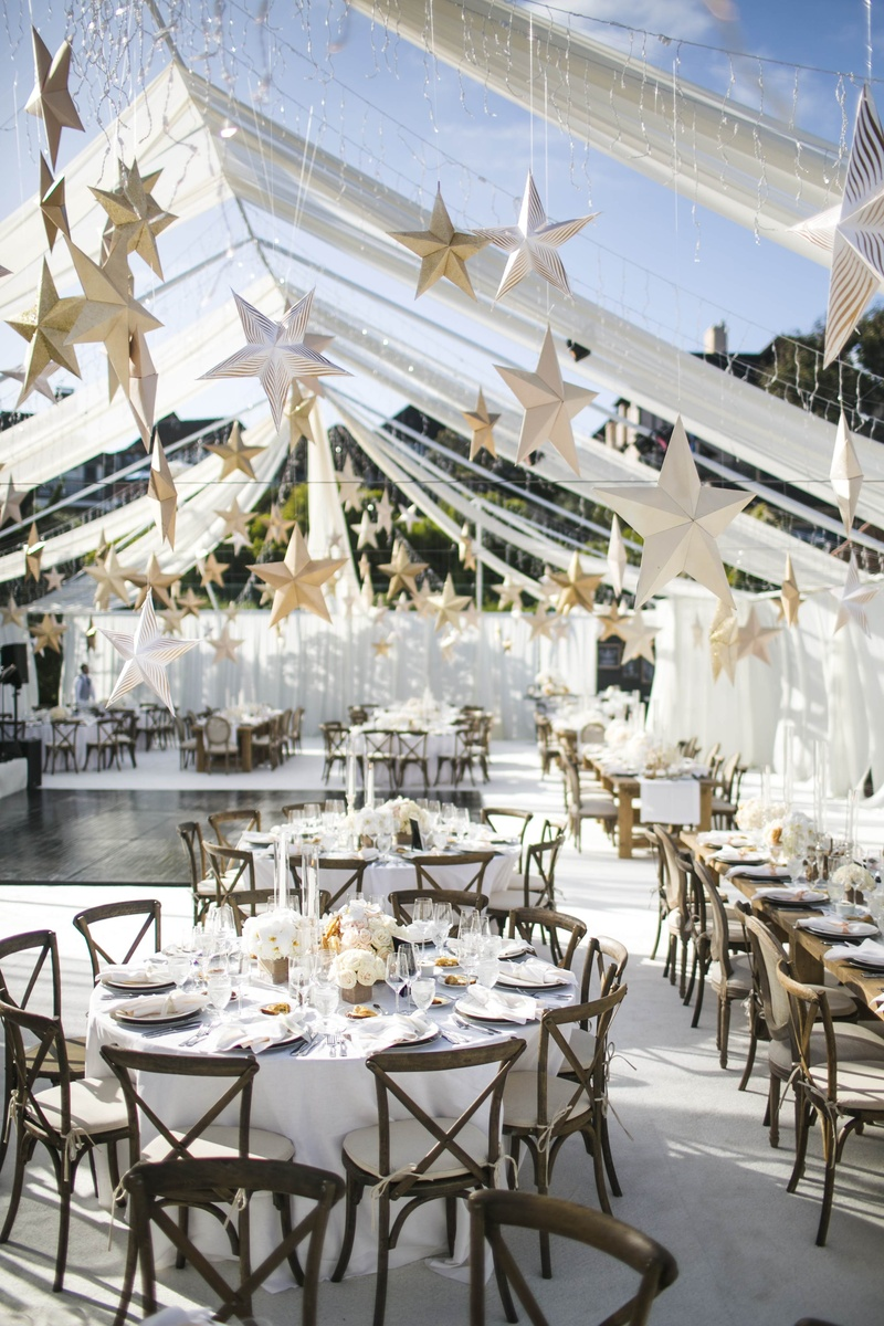 Gold paper stars suspended from ceiling over tables