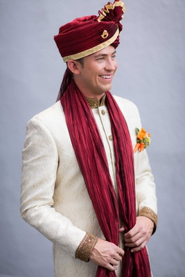 Caucasian groom in white sherwani and red turban for Hindu wedding ceremony