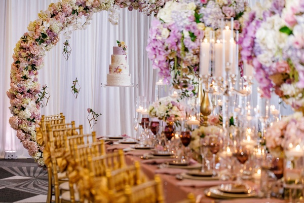Wedding reception spring table inspiration gold chairs floating cake flower arc matching centerpiece