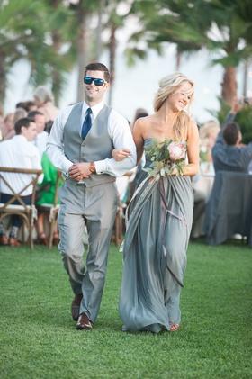 Garden wedding with bridesmaid in strapless light grey dress, protea, greenery bouquet, groomsman