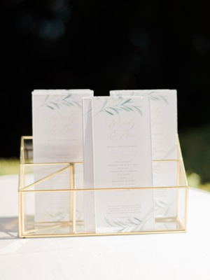 wedding ceremony gold display white ceremony program greenery flower motif muted