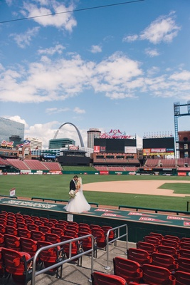 Wedding portrait couple photo at Busch baseball Stadium in St. Louis with Gateway Arch in background