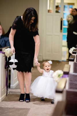 Woman in black lace dress and peep toe booties helping baby flower girl walk down aisle ceremony