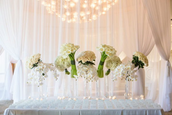 wedding reception escort card table seating assignments white drapery collections of white flowers