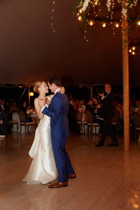 bride in classic wedding dress groom in blue suit dancing on wood floor to first dance song