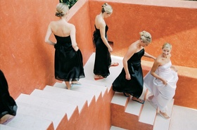 Bridal party next to orange walls at El Carayes Resort