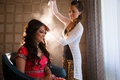 Hair stylist sprays hairspray on Indian bride's curled wedding hairstyle