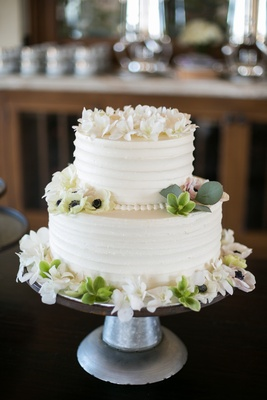 two-tier wedding cake with buttercream frosting and floral details