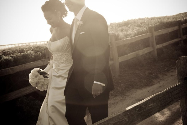 Bride and groom walk along oceanfront trail