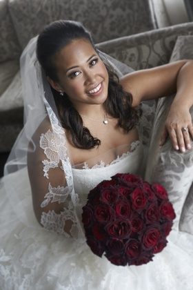 bride in vera wang with round bouquet of dark red roses