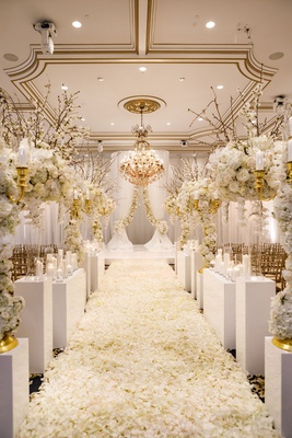 white and gold ballroom wedding ceremony white flower petals arrangements gold molding chandelier