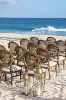 beach wedding ceremony decor round back wood cane chairs white cushions gold lantern white sand