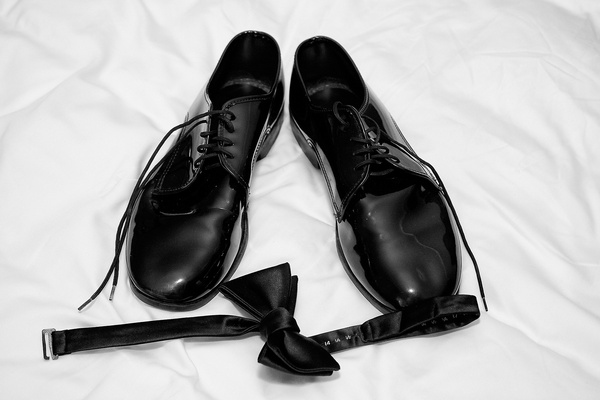 grooms black dress shoes and bow tie on white sheet
