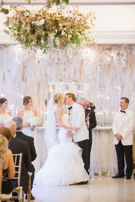 Bride in Hayley Paige mermaid gown kissing groom in white tuxedo jacket white ribbon ceremony decor