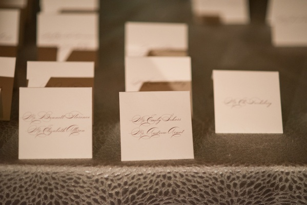 small white escort cards with names written in gray calligraphy