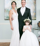 bride in rivini wedding dress, groom in tux and white neck tie, flower girl in full ball gown