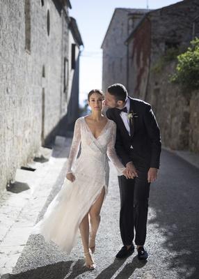 newlyweds walk through Italian village holding hands, groom kisses bride on the cheek