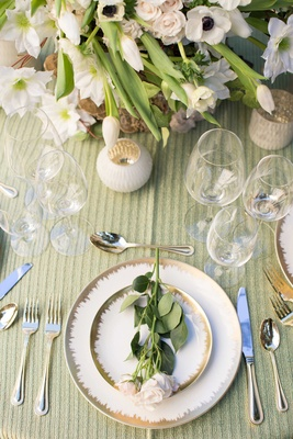 white and gold charger plates on green table linen pink stem flowers silverware floral arrangement